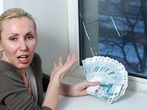 The housewife cries and counts money for repair of a window which has burst in a frost Royalty Free Stock Images