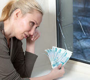 The housewife cries and counts money for repair of a window which has burst in a frost. The housewife cries and counts money for repair of a window which has Stock Photo