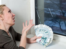 The housewife cries and counts money for repair of a window which has burst in a frost Stock Images