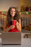 Housewife with cup of hot chocolate using laptop Royalty Free Stock Photography