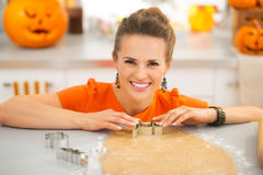 Housewife cutting out Halloween cookies in kitchen Stock Photography