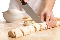 Housewife cutting sweet rolls on the wooden board Royalty Free Stock Photo