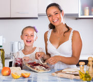 Housewife with daughter cooking apple pie Royalty Free Stock Photo