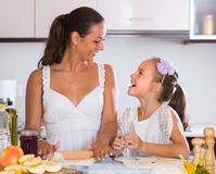 Housewife with daughter cooking apple pie Royalty Free Stock Photography