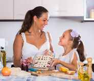 Housewife with daughter cooking apple pie Stock Image