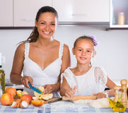 Housewife with daughter cooking apple pie Royalty Free Stock Photos