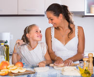 Housewife with daughter cooking apple pie. Cheerful young women with daughter preparing apple pie in home kitchen Stock Photo
