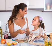 Housewife with daughter cooking apple pie Stock Photography