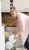 Housewife at the dishwasher Royalty Free Stock Photography