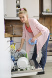 Housewife at the dishwasher Stock Image