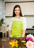 Housewife doing  bouquet on  kitchen table Royalty Free Stock Photos
