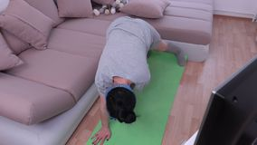 Housewife doing exercises near TV. In room stock footage