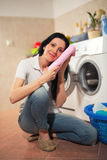 Housewife is doing laundry with washing machine at home. Royalty Free Stock Photos