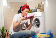 Housewife is doing laundry with washing machine at home. Royalty Free Stock Photo