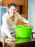 Housewife doing regular clean up in living room Stock Image