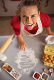 Housewife drawing christmas tree on kitchen table with flour Royalty Free Stock Image