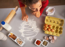 Housewife drawing christmas tree on kitchen table with flour Stock Image