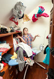 Housewife in dressing room with clothes flying around Stock Photo