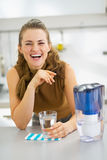 Housewife drinking water from water filter pitcher in kitchen Royalty Free Stock Images