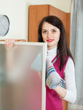 Housewife dusting glass of furniture Royalty Free Stock Photos