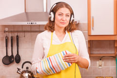 Housewife with earphones in kitchen Stock Photography