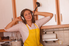 Housewife with earphones in kitchen Royalty Free Stock Photo