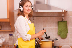 Housewife with earphones in kitchen Royalty Free Stock Photography