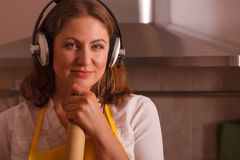 Housewife with earphones in kitchen Stock Images