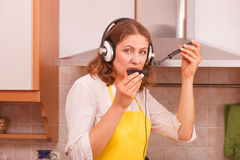 Housewife with earphones in kitchen Royalty Free Stock Image