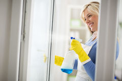 Housewife easy wash windows with appropriate cleanser. In bottle with spray Stock Photos