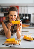 Housewife eating boiled corn in kitchen Royalty Free Stock Images