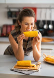 Housewife eating boiled corn in kitchen Royalty Free Stock Image
