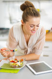 Housewife eating fruits salad and using tablet pc. Happy young housewife eating fruits salad and using tablet pc stock image