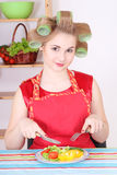 Housewife eating salad in the kitchen Royalty Free Stock Images