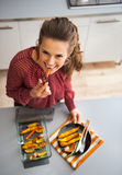Housewife eating while serving baked pumpkin Royalty Free Stock Photos