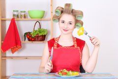 Housewife eating vegetables in the kitchen Stock Image