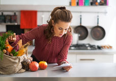 Housewife exploring checks after grocery shopping Stock Images