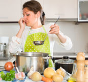 Housewife feeling bad smell from pan. Housewife pinched her nose avoiding bad smell from pan royalty free stock image
