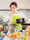 Housewife feeling bad smell from pan. Young housewife pinched her nose avoiding bad smell from pan royalty free stock photography