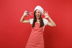 Housewife female chef cook or baker in striped apron, white t-shirt, toque chefs hat isolated on red wall background stock image