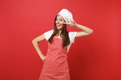 Housewife female chef cook or baker in striped apron white t-shirt toque chefs hat isolated on red wall background stock photography