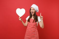 Housewife female chef cook or baker in striped apron, white t-shirt, toque chefs hat isolated on red wall background