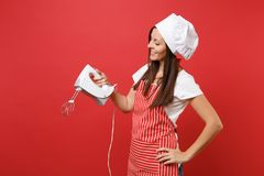 Housewife female chef cook or baker in striped apron white t-shirt toque chefs hat isolated on red wall background royalty free stock images
