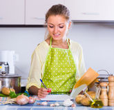 Housewife filling documents at kitchen Stock Photography