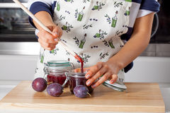 Housewife filling the jar with jam Royalty Free Stock Photo