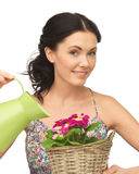 Housewife with flower in basket and watering can Stock Photos