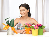 Housewife with flower in pot and gardening set Stock Images