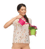 Housewife with flower in pot and watering can Stock Photos
