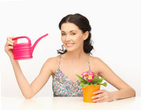 Housewife with flower in pot and watering can Royalty Free Stock Photography