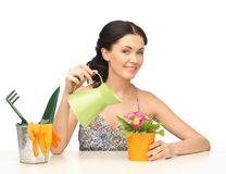 Housewife with flower in pot and watering can Stock Photography